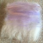 merino wool base layer laid out for felting with a wash of colour for the sky